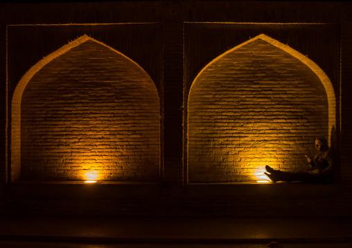 man resting under an arch at si-o-seh bridge, Isfahan Province, isfahan, Iran