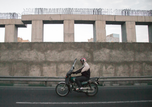 elderly iranian man riding a motorbike on a highway, Central district, Theran, Iran