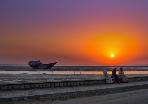 men dressed in traditional dress, sitting on a bench in front of a sunset and a dhow boat, Qeshm Island, Laft, Iran