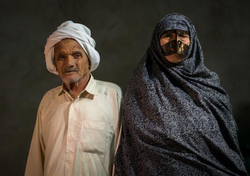 a bandari woman wearing a traditional mask called the burqa with her husband, Qeshm Island, Tabl , Iran