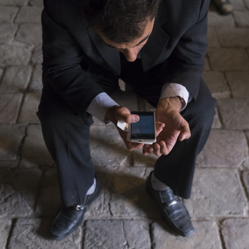 Man reading a pray on his mobile phone inside the friday mosque, Isfahan province, Isfahan, Iran