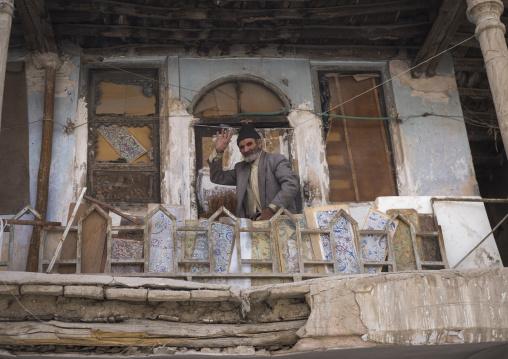 Man waving hello on the balcony of his old house, Isfahan province, Isfahan, Iran