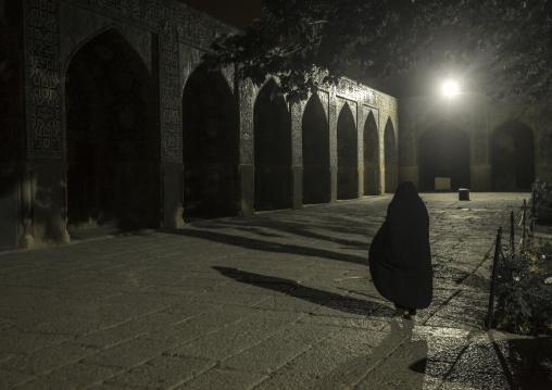 Iranian veiled woman inside sheikh lotfollah mosque at night, Isfahan province, Isfahan, Iran