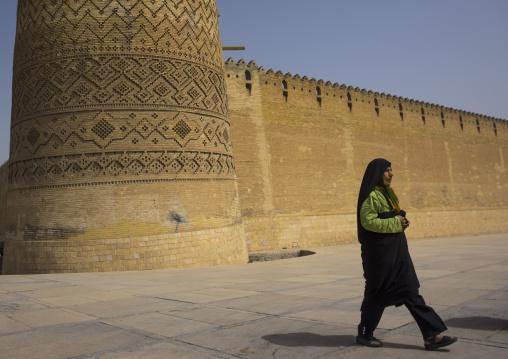 Woman passing in front of karim khan fort or arg e karim khan, Fars province, Shiraz, Iran