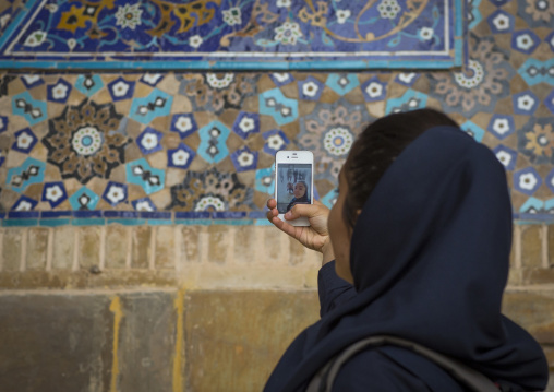Iranian tourist taking picture with her mobile phone inside the friday mosque, Isfahan province, Isfahan, Iran