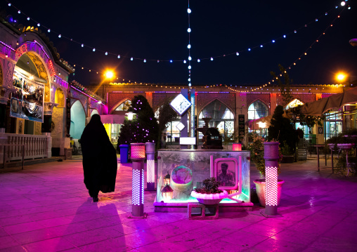 Iranian woman in chador going inside a mosque illuminated for Muharram to commemorate the martyrdom anniversary of Hussein, Isfahan Province, Isfahan, Iran