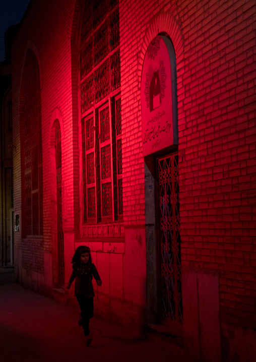 Iranian girl running in a street illuminated with red light for Muharram to commemorate the martyrdom anniversary of Hussein, Isfahan Province, Isfahan, Iran