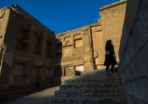 One iranian girl walks in the the ruined houses of the old part of the town, Isfahan Province, Isfahan, Iran