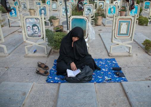Portrait of an iranian shiite mother mourning in the rose garden of martyrs cemetery, Isfahan Province, Isfahan, Iran