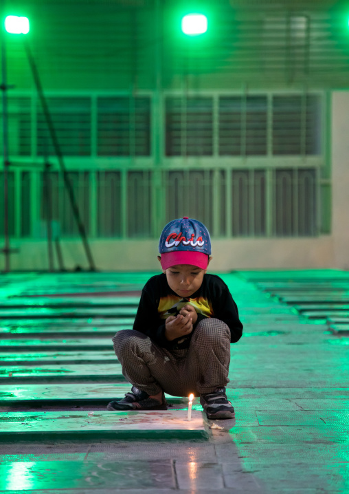 Portrait of an iranian shiite boy putting a candle on a tomb in the rose garden of martyrs cemetery, Isfahan Province, Isfahan, Iran