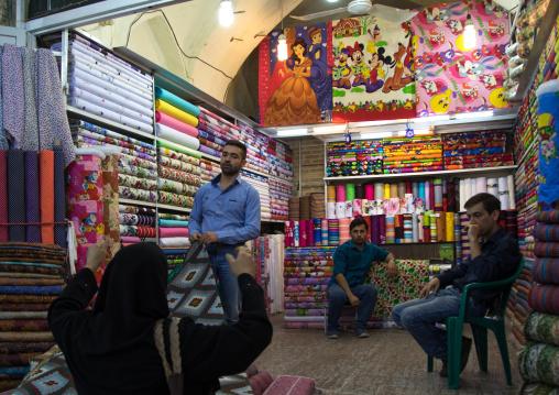 Man selling Disney stuff i the clothes Bazaar, Fars Province, Shiraz, Iran