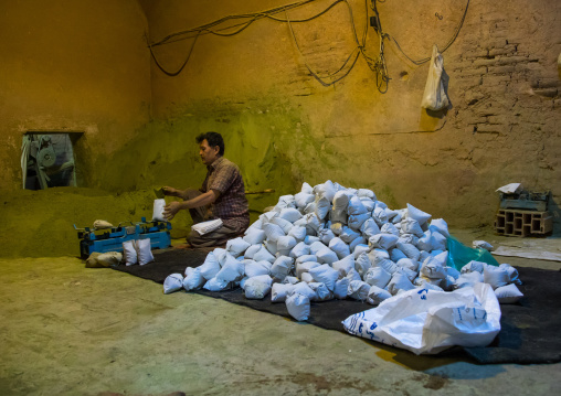 Afghani worker packing henna bags in a traditional mill, Yazd Province, Yazd, Iran