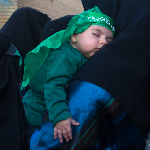 Iranian shiite muslim baby dressed for Muharram and sleeping on her mother shoulder, Lorestan Province, Khorramabad, Iran
