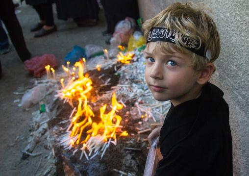 Iranian boy lights candles during Chehel Manbar ceremony on Tasua to commemorate the martyrdom anniversary of hussein, Lorestan Province, Khorramabad, Iran
