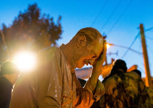 Iranian shiite muslim man crying after rubbing mud on his body during the Kharrah Mali ritual to mark the Ashura ceremony, Lorestan Province, Khorramabad, Iran