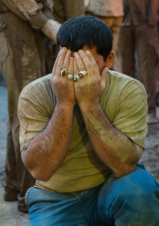 Iranian shiite muslim man crying after rubbing mud on his body during the Kharrah Mali ritual to mark the Ashura day, Lorestan Province, Khorramabad, Iran