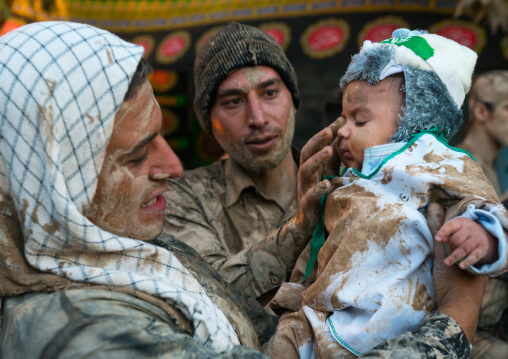 Iranian shiite muslim men rubbing mud on a baby during the Kharrah Mali ritual to mark the Ashura day, Lorestan Province, Khorramabad, Iran