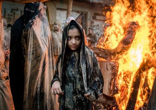 Iranian shiite muslim girls gather around a bonfire after rubbing mud on their chadors during the Kharrah Mali ritual to mark the Ashura day, Lorestan Province, Khorramabad, Iran