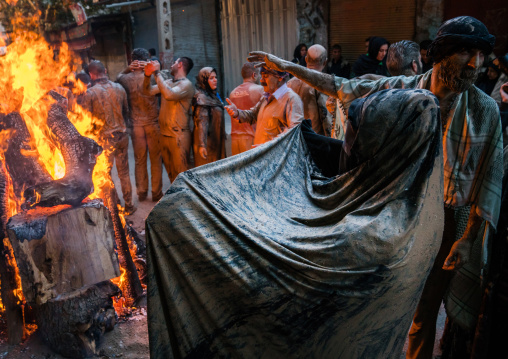 Iranian shiite muslim men and women gather around a bonfire after rubbing mud on their clothes during the Kharrah Mali ritual to mark the Ashura day, Lorestan Province, Khorramabad, Iran