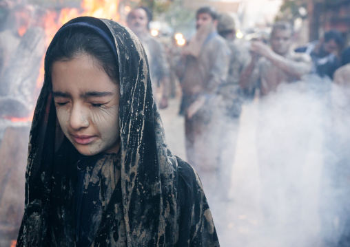 An Iranian shiite muslim girl with closed eyes stands in front a bonfire after rubbing mud on her chador during the Kharrah Mali ritual to mark the Ashura day, Lorestan Province, Khorramabad,