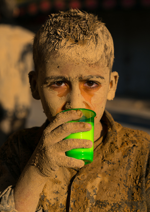 Iranian shiite muslim boy drinks milk after rubbing mud on his body early in the morning of Ashura day, Lorestan Province, Khorramabad, Iran