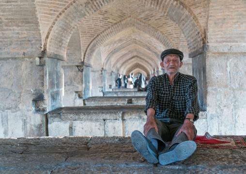 Old man resting under Khaju bridge Pol-e Khaju, Isfahan Province, Isfahan, Iran