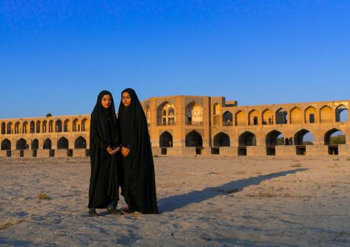 Portrait of two young women in chadors in front of Khaju bridge Pol-e Khaju, Isfahan Province, Isfahan, Iran