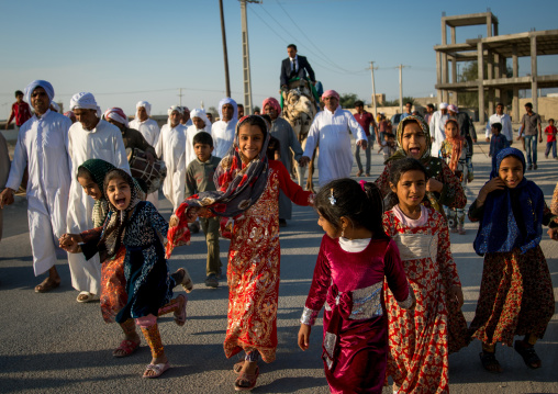 girls running in front of a groom riding his camel during the wedding ceremony, Qeshm Island, Salakh, Iran