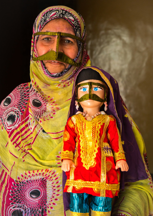 a bandari woman wearing a traditional mask called the burqa with a decorated doll for nowruz festival, Qeshm Island, Salakh, Iran