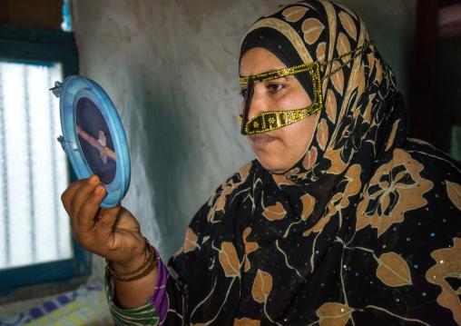 a bandari woman wearing a traditional mask looking herself in a mirror, Qeshm Island, Salakh, Iran