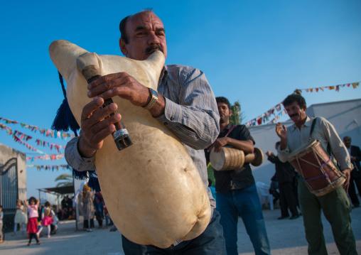 men dancing and playing sheep skin pipe bag during a wedding ceremony, Hormozgan, Kushkenar, Iran
