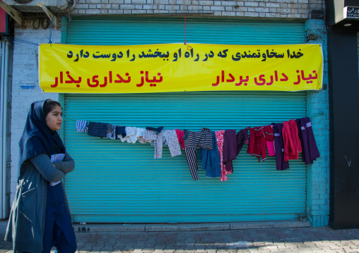 woman passing in front of a wall of kindness created to give clothes for free to poor people, Central County, Yazd, Iran