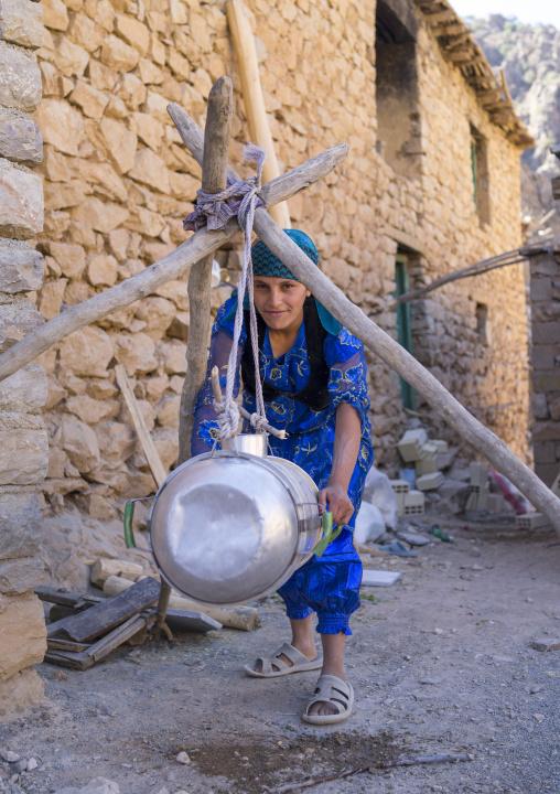 Woman Shaking Milk In The Old Kurdish Village Of Palangan At Dusk, Iran