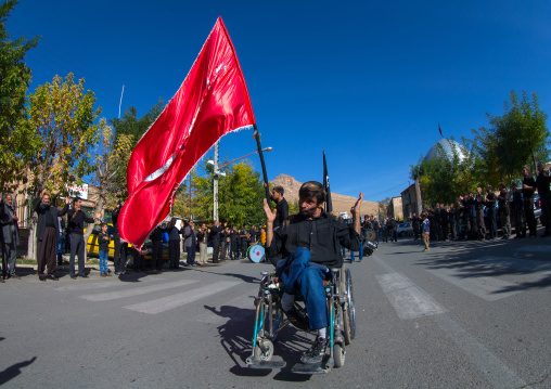 Man In Wheelchair In Front Of A Red Flag Celebrating Ashura, The Day Of The Death Of Imam Hussein, Kurdistan Province, Bijar, Iran