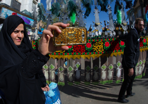 Iranian Woman Taking Pictures With A Mobile Phone Branded Louis Vuitton During Ashura, The Day Of The Death Of Imam Hussein, Kurdistan Province, Bijar, Iran