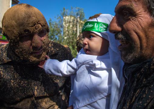 Iranian Shiite Baby Touching The Beard Of A Man Covered In Mud During Ashura Day, Kurdistan Province, Bijar, Iran