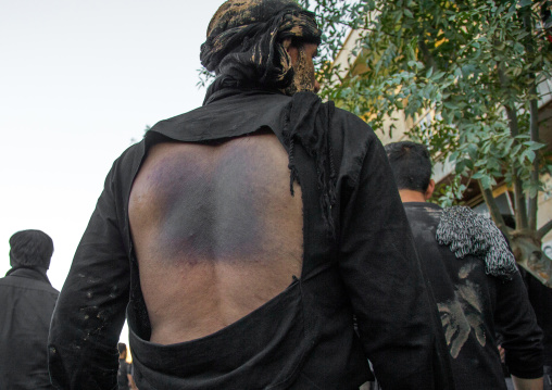 Iranian Shiite Man Covered In Mud Who Has Beaten Himself His Back With Iron Chains During Ashura, The Day Of The Death Of Imam Hussein, Kurdistan Province, Bijar, Iran