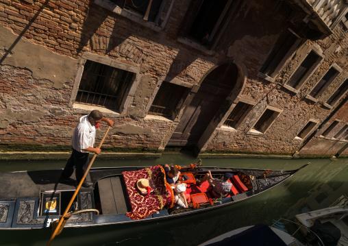 Gondola on a canal with tourists, Veneto Region, Venice, Italy