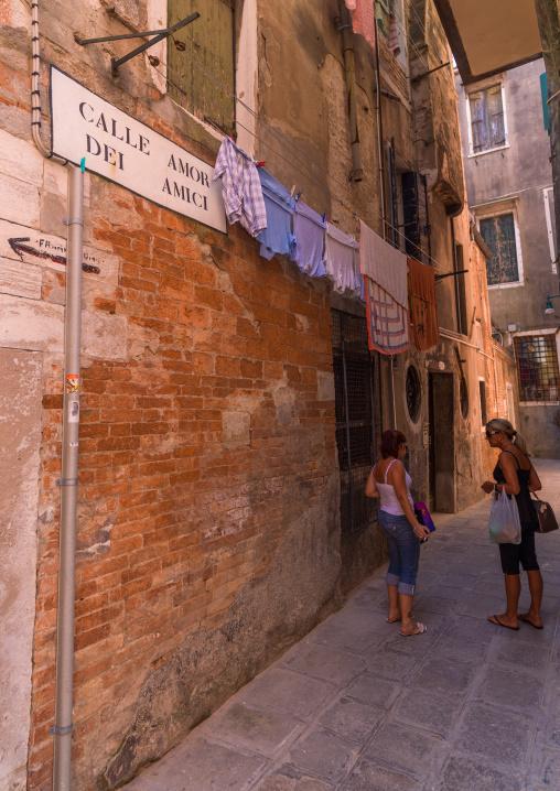 Italain women chatting in a narrow street of the old town, Veneto Region, Venice, Italy