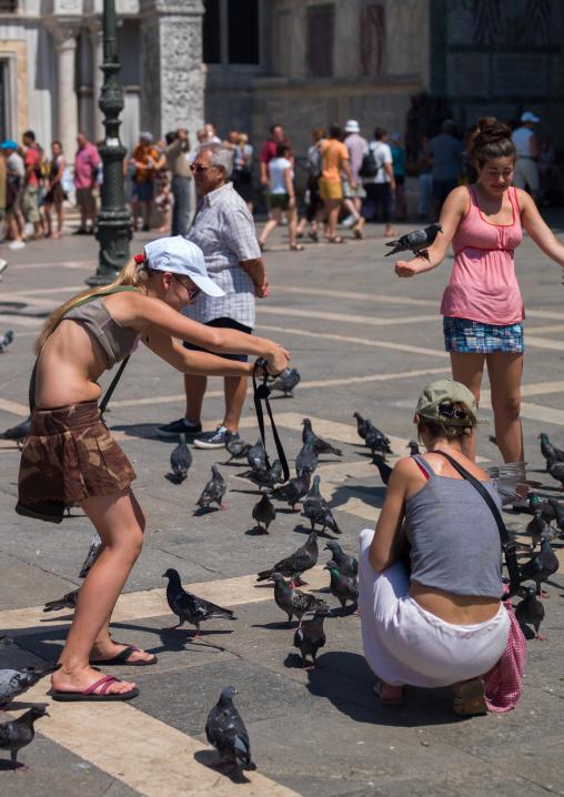 Tourists feeding pigeons in st. Mark's square, Veneto Region, Venice, Italy