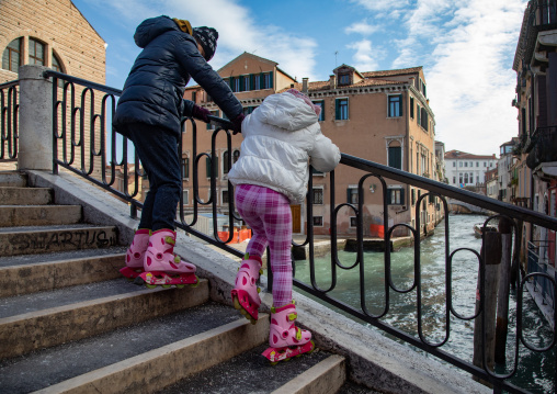 Mother and girl with  roller-skates on a stair in the old town, Veneto, Venice, Italia