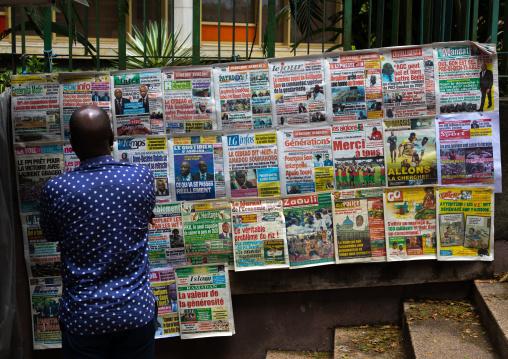 African man reading newspapers displayed on a market stall, Région des Lagunes, Abidjan, Ivory Coast