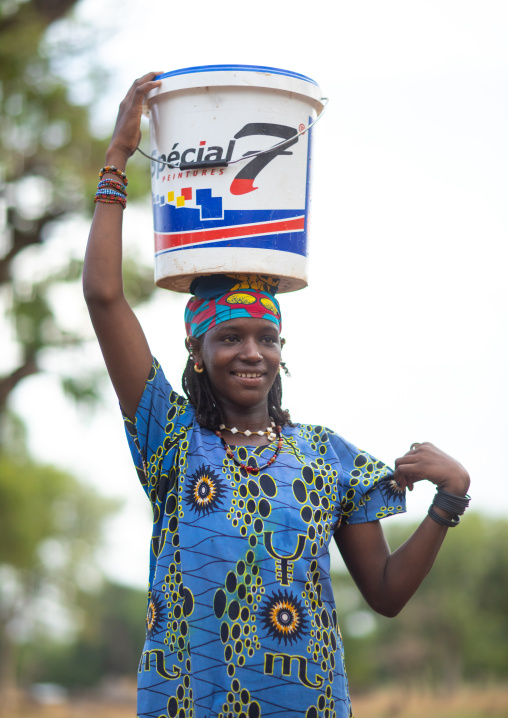 Portrait of a Peul tribe girl carrying a bucket full of water on the head, Savanes district, Boundiali, Ivory Coast