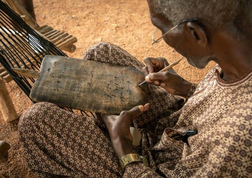 Senior man sit on a hammock writing koran on a wood board, Savanes district, Kouto, Ivory Coast