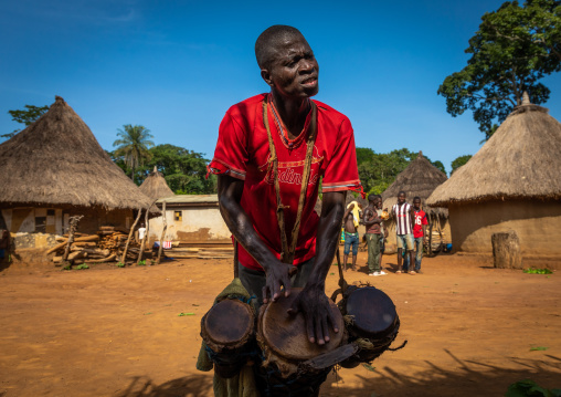 Dan tribe man beating the drums during a ceremony, Bafing, Gboni, Ivory Coast