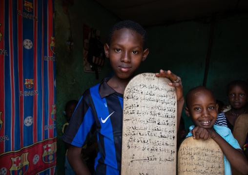Children with wood boards for writing koran in a koranic school, Tonkpi Region, Man, Ivory Coast