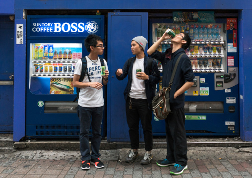 Young men using a drinks vending machine, Kanto region, Tokyo, Japan