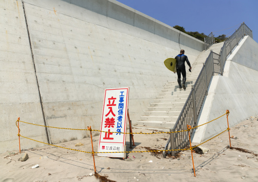 A authorized entry prohibited sign in front of a japanese surfer in the contaminated area after the daiichi nuclear power plant irradiation, Fukushima prefecture, Tairatoyoma beach, Japan