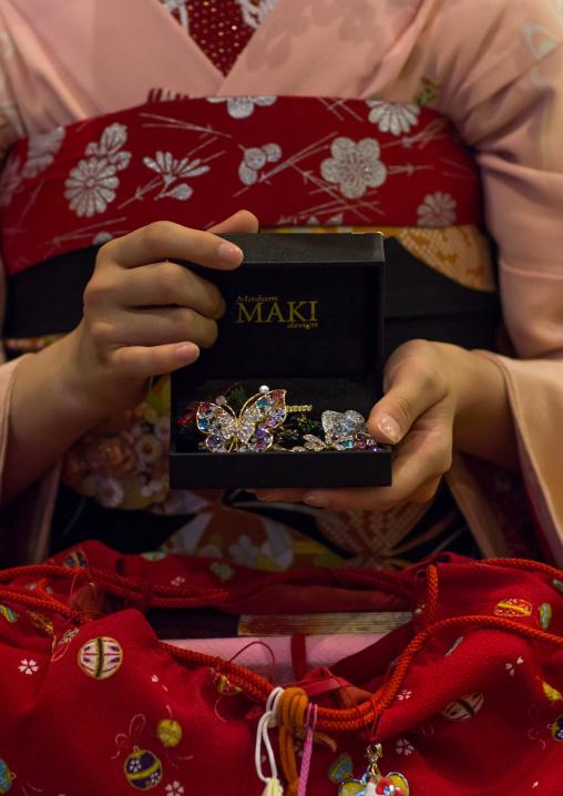16 Years old maiko called chikasaya showing her brooches, Kansai region, Kyoto, Japan