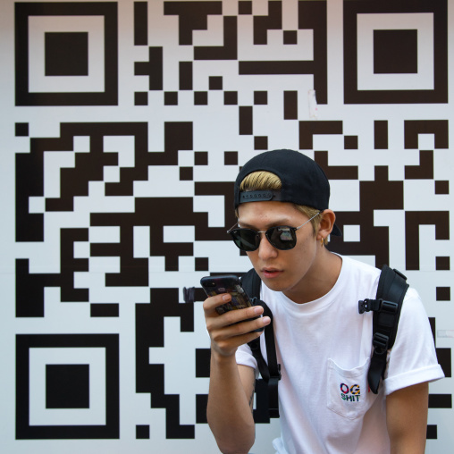 Young japanese man looking at his mobile phone in front of a giant bar code, Kanto region, Tokyo, Japan